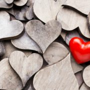 A Single Red Love Heart on Pile of Plain Wooden Hearts – What Does Love Mean - Sandra Harewood Counselling