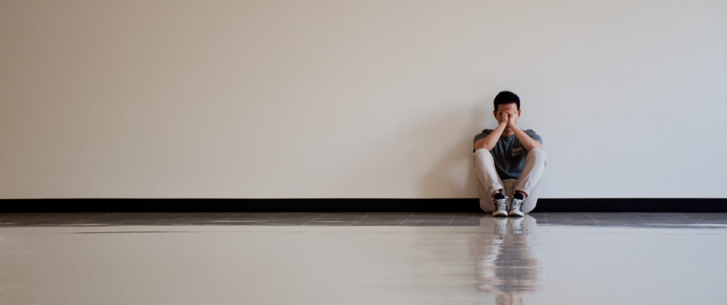A sad man sitting alone against a wall in an empty room - Sandra Harewood Counselling - Counselling for Depression