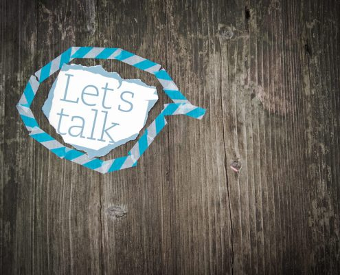 Let's Talk Note in Blue Speech Bubble on Wooden Surface - Your First Counselling Session - Sandra Harewood Counselling