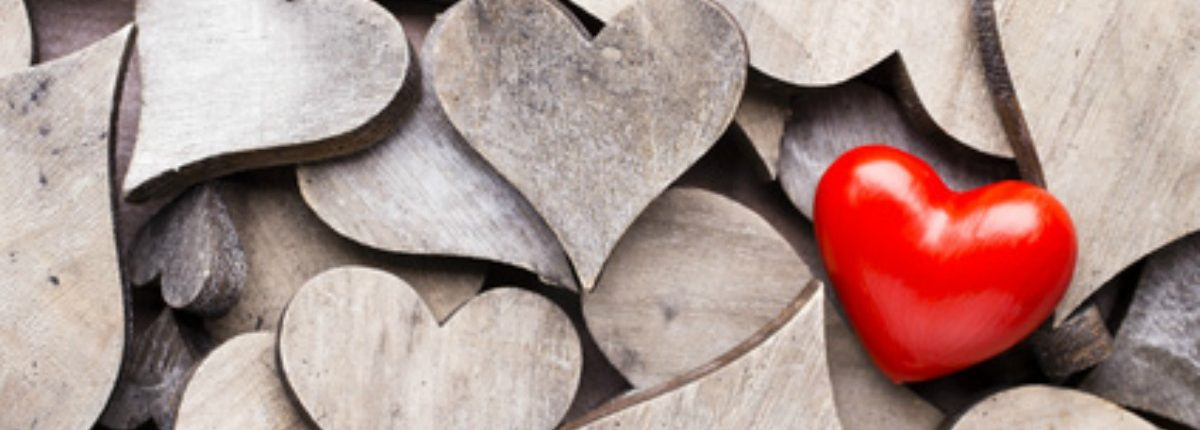 A Single Red Love Heart on Pile of Plain Wooden Hearts - Sandra Harewood Counselling