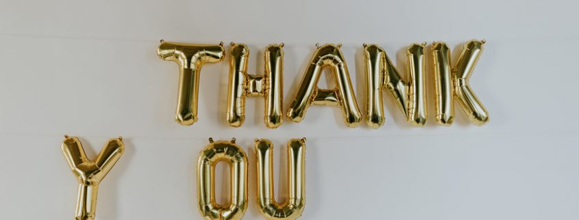 "Gold ""THANK YOU"" balloon letters hanging on the wall =How Showing Your Partner Appreciation Can Help Improve Your Relationship - Sandra Harewood Counselling"