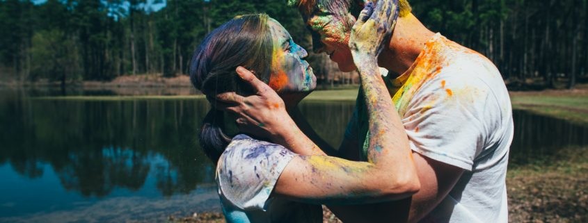 Couple Throwing Colored Holi Powder at Each Other For Fun - 24 Ways To Be Playful With Your Partner - Sandra Harewood Counselling