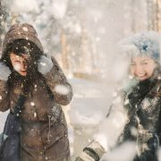 Two joyful friends having fun in the snow during on a cold winter's day. Christmas can be stressful so it's important to spend some time to relax and take care. This post shows you one great way how to Stay Relaxed At Christmas Sandra Harewood Counselling
