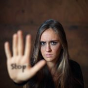 Frightened woman with her arm outstretched with the word stop written on her hand. The Honest Truth About Your Partner's Anger Issues. Sandra Harewood Counselling