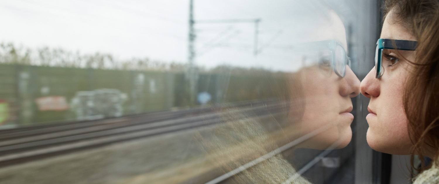 Young woman looking through the train window with a serious mood - Echo's Story - How Living With Narcissism Affects You - Sandra Harewood Counselling