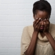 Black Woman Holding Her Head In Her Hands -What A Blue Fish Tells You About Your Anxiety - Sandra Harewood Counselling