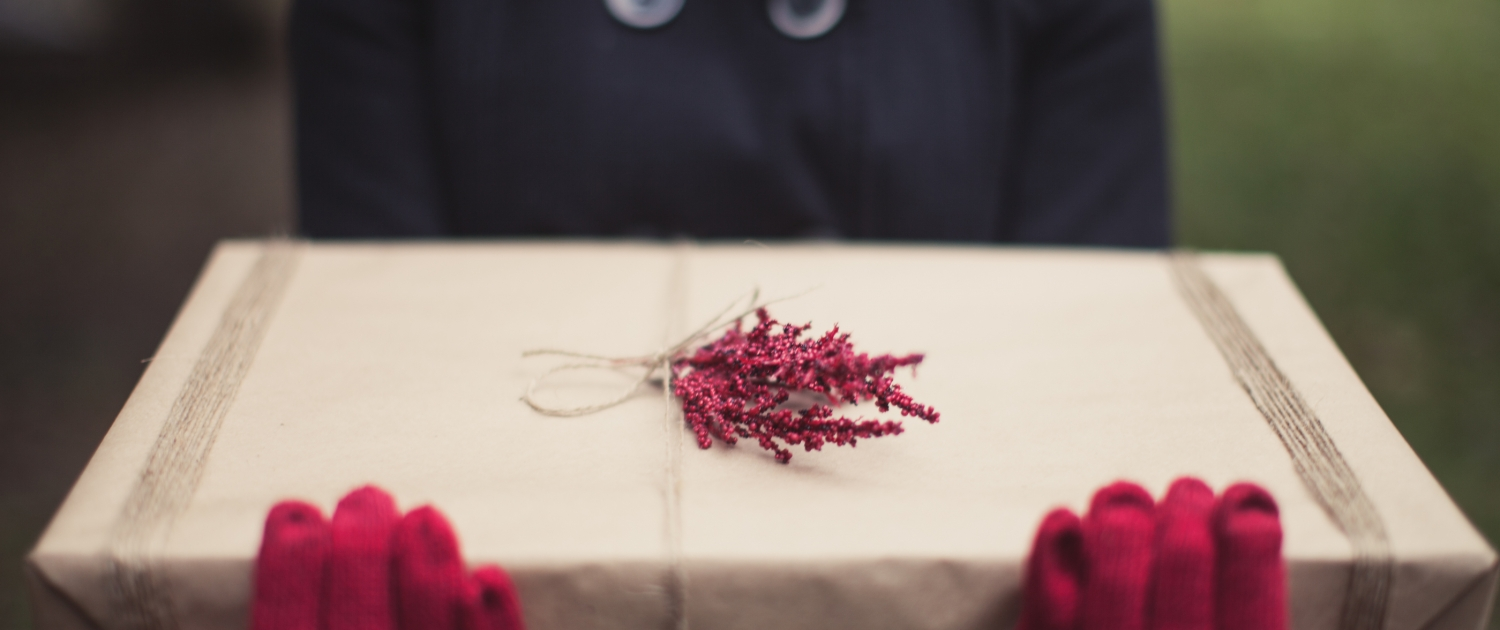 A woman wearing red gloves holding a gift wrapped in brown paper - 5 Great Gifts To Give Yourself This Christmas - Sandra Harewood Counselling