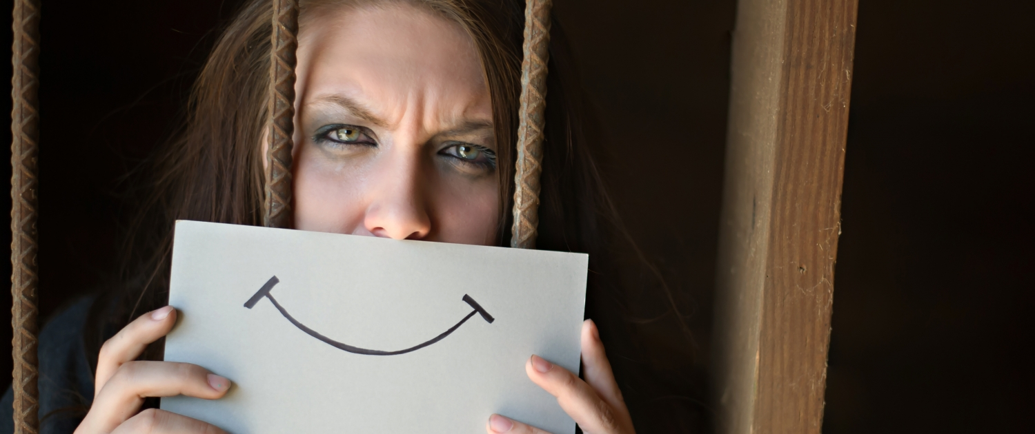 Woman Hiding Behind a Smiley Face Picture, Behind Bars - Coercive Control: 7 Reasons Why Women Don't Leave - Sandra Harewood Counselling