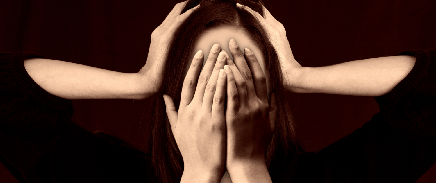 Stressed Woman With Her Hands Covering Her Face - What Your Physical Symptoms Can Teach You About Hidden Stress