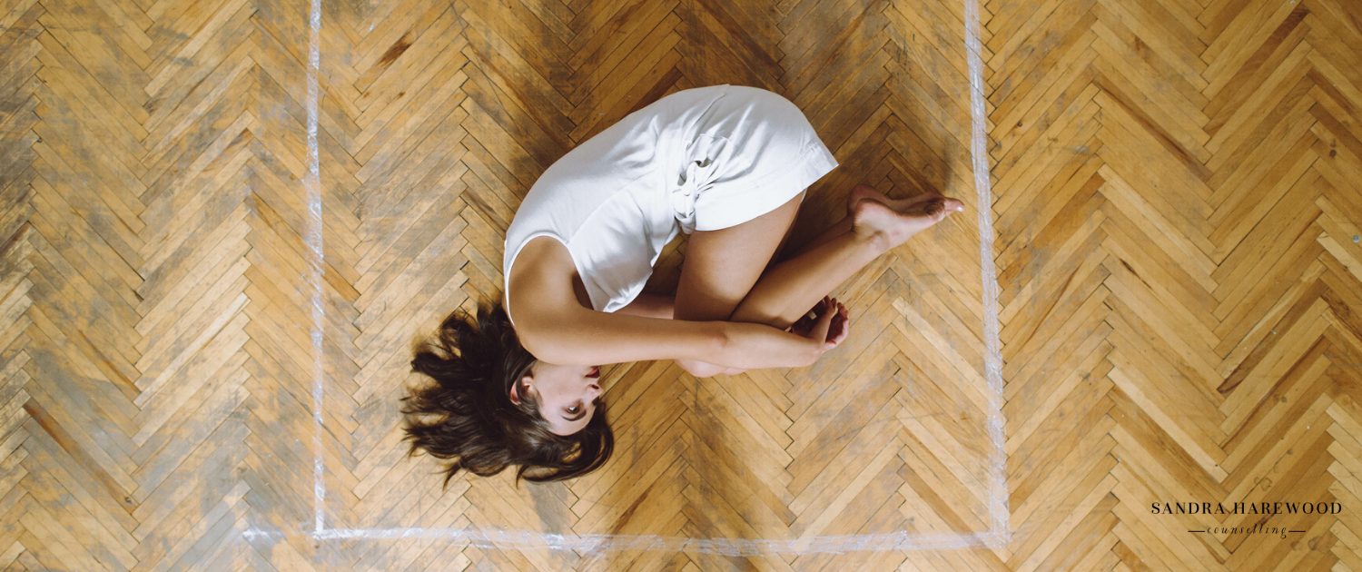A young beautiful black-haired girl dressed in a white T-shirt and white shorts lying on her side in a room on a wooden parquet in a square painted with a white paint, bending her legs in a lap and pressing them against her chest and hugging them with a hands. Top view - How To Protect Yourself When Self-Isolating With A Controlling Partner - Sandra Harewood Counselling