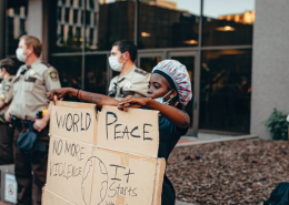 Black Woman Holding Cardboard Banner With World Peace Written On It Surrounded By White Policemen- Why Racism Is Like Being In An Abusive Relationship - Sandra Harewood Counselling